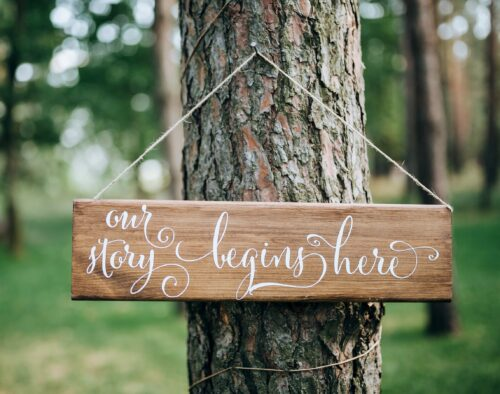 """In a small forest outside, on a tree trunk a wooden sign reads, """"Our story begins here"""""""