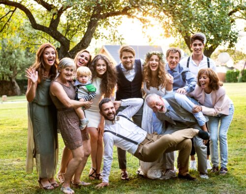 A family posing for a group photo at a wedding, outside at sunset. The bride an groom are standing in the center and the family poses around them. One man is posing horizontally with his right arm holding him up, his left hand is behind his head (elbow bent), his left leg supporting him and his right leg crossing and resting on his left leg. An elderly man is leaning over him and laughing.