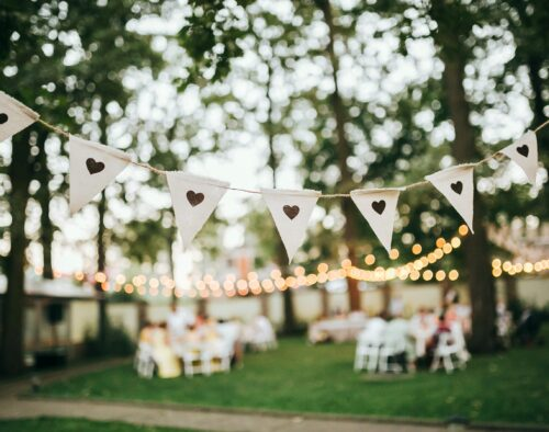 A bunting hung with twine. Each triangle flag is white with a gray stamped heart in the center. In the background is an outdoor wedding reception with trees, lights, tables and chairs
