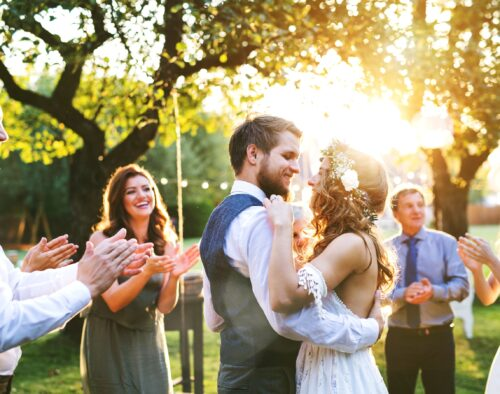 A bride and groom dancing together at an outdoor wedding reception at sunset. Guests are standing around them and clapping. There are a couple of trees in the background.