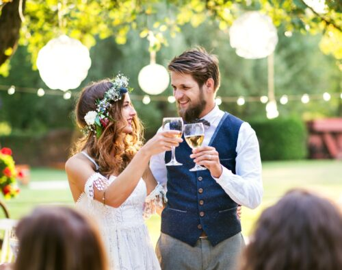 At a wedding reception outdoors. A bride and groom touching wine glasses in a toast. There are guests heads in the foreground and lights, trees and decorations.