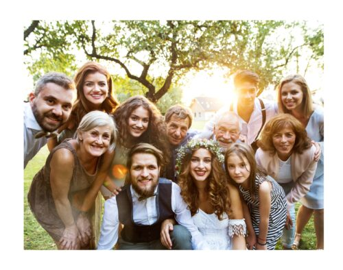 A family posing together outdoors at a wedding. The bride and groom are crouched at the bottom and the rest of the family is leaning in around them. The sun is setting through some trees