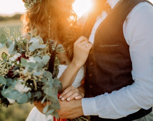 A close-up of a bride and groom facing each other. Their heads are mostly out of frame. The bride's hand is on the groom's chest, showing her ring. The groom is holding the bouquet in the foreground.