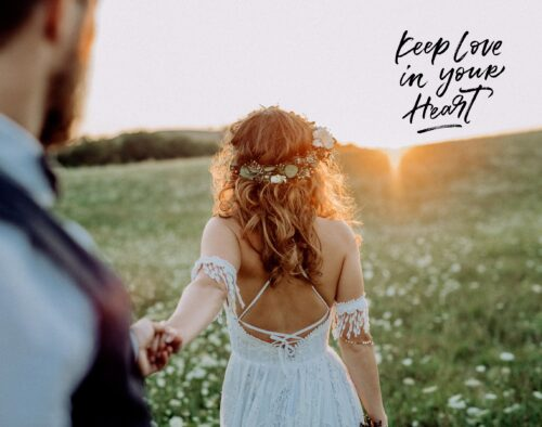 """There is text in the top right that says, """"Keep love in your heart"""". On a grassy hill outdoors, a bride, holding a groom's hand, leads him towards the sunset"""