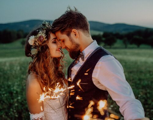 A bride and groom facing each other with their foreheads touching. There is a sparkler in the foreground and a hilly landscape, with a few trees in the background.